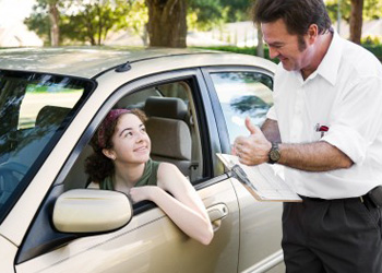 Girl in vehicle with driving instructor