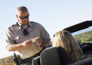 Traffic citation for speeding being issued to driver by Michigan Highway Patrol officer